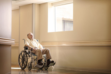 Senior man in wheelchair in corridor