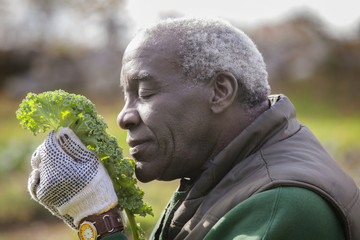 Close up of man smelling kale in garden