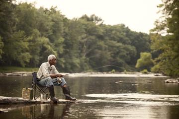 Senior man fishing by river