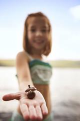 Girl (6-7) showing acorn on hand