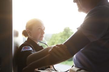 EMT checking blood pressure of senior man