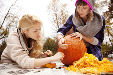 Two friends carving pumpkin for Halloween
