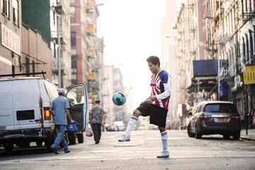 Sportsman playing soccer on city street