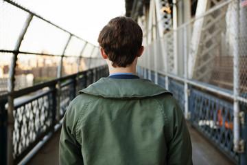 Rear view of man walking on pedestrian walkway of Manhattan Bridge