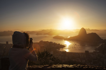 Woman photographing sunrise at sea bay