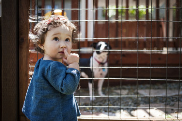 Cute girl standing next to dog's cage