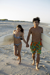 Asian-american couple carrying surfboards at beach