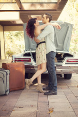 Couple embracing while packing up car