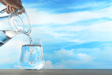 Foto op Textielframe Water Fresh and clean drinking water being poured from jug into glass on sky background