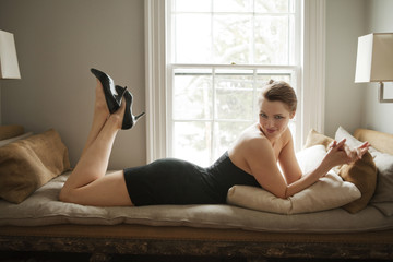 Woman lying on couch in black dress