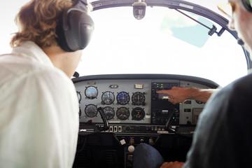 Mechanics examining cockpit of airplane