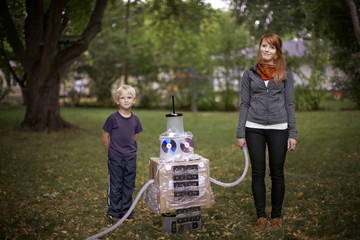 Brother (4-5) and sister posing with their robot