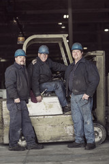 Portrait of factory workers on forklift