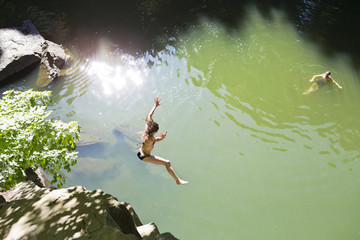 Woman jumping off rock into lake