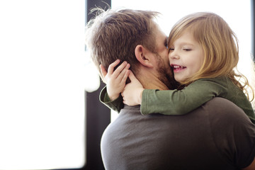 Happy father embracing daughter at home