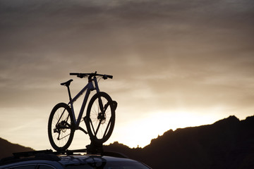Low angle view of bicycle on car roof against cloudy sky during sunset