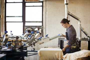 Female worker printing on t-shirt in works