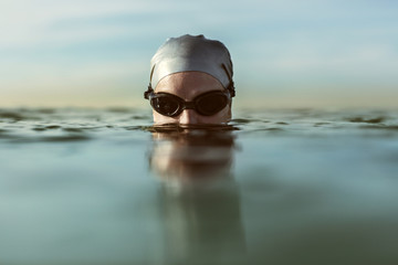 Surface level of swimmer in sea during sunset