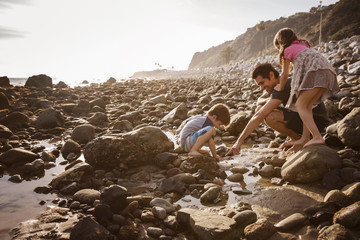 Father and children (4-5, 6-7) on beach