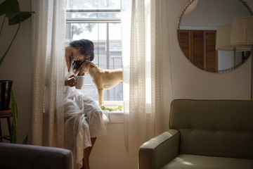 Woman with dog sitting on window sill at home