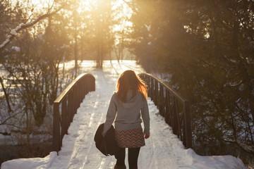 Young woman crossing snowy bridge