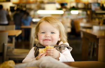 Girl (18-23 months) eating in food court
