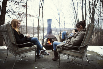 Two women sitting by outdoor fireplace