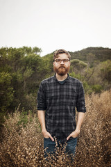 Portrait of hipster standing in field