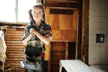 Girl (8-9) with hammer tool belt and safety glasses