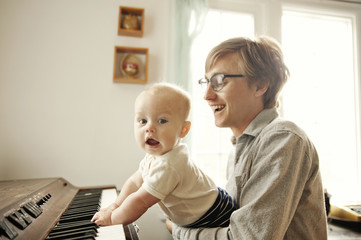 Father holding his baby son (6-11 months) who is playing piano