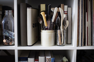 Cutleries in containers on bookshelves