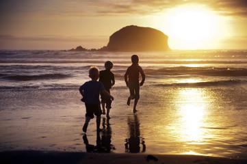 Kids (8-9, 6-7, 2-3) running into ocean at sunset