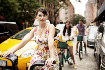 Portrait of woman riding bicycle with friends in background