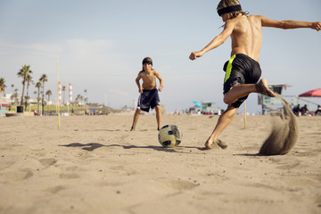 Boys playing soccer at beach against sky