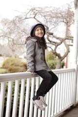 Girl (6-7) sitting on porch railing