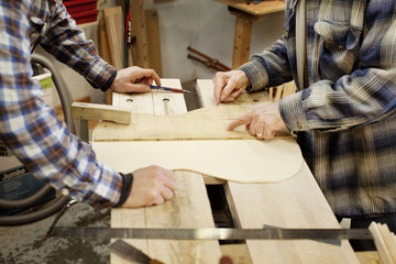 Two men measuring wood for guitar