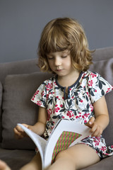 Girl (2-3) sitting on sofa and reading book
