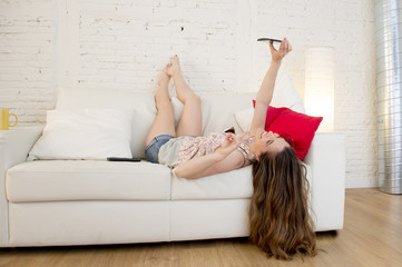 happy attractive girl playing on home couch taking selfie portrait with mobile phone having fun