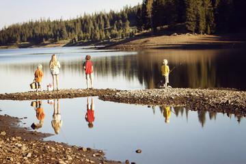 Siblings fishing in river