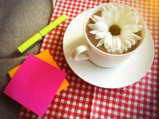 coffee cup on table with white daisy and sticky note, pen vintag