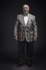 Portrait of senior man standing against black background