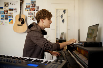 Young man playing piano in bedroom