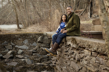 Father and daughter sitting on stone wall