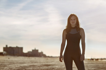 Portrait of confident swimmer standing against sky