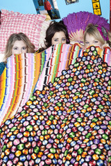 Three women hiding under bed covers