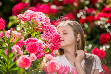 Beautiful girl standing in the park of roses.