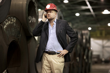 Mature manager wearing hardhat using mobile phone in warehouse