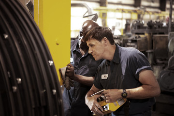 Men checking machinery in factory
