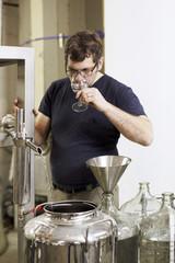 Brewer sampling liquor at distillery