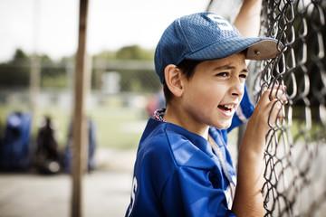 Boy looking through fence on field